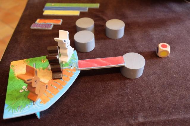 Les trois lapins (oui, parce qu'on joue à 3 : Tristan avec le marron foncé, Leila avec le blanc et moi-même avec le marron clair) sont en attente sur une rive du grand lac qui se trouve face à eux. A son tour, on jette un dé, lequel va indiquer le pont à utiliser pour ce tour. Sans autre aide que le regard, distant, pas le droit d'approcher le pont du lac, ... on va essayer de placer une pierre (disque gris) et vérifier que le pont tient. Ci-dessus, Leila réussit un superbe premier coup avec le pont rouge ! Quelle optimisation...