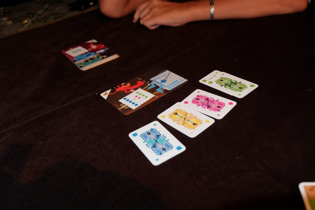 Le principe est le suivant : une carte d'œuvre, requérant des couleurs en une certaine quantité, est exposée sur la table au centre (ici : 4 vert, 2 rouge, 1 jaune et 5 bleu). A tour de rôle, les joueurs ont le choix entre : 1/ ajouter autant de cartes qu'ils le souhaitent (à droite de l'œuvre ci-dessus) ou 2/ gribouiller l'œuvre (en plaçant une et une seule carte non demandée à gauche de l'œuvre). L'équipe qui place la dernière carte à droite ou la 3ème à gauche remporte la carte d'œuvre. Si l'œuvre était réussie, l'équipe empoche beaucoup de $, si l'œuvre termine barbouillée, l'équipe en empoche la moitié. Le but est de totaliser un score de 25$.