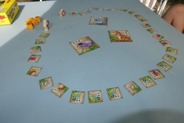 Sur la table, l'ensemble des petite tuiles carrées d'animaux (proies à chasser tout au long de la partie) est étalé en forme de cercle, avec deux figurines en bois, dos à dos, au bout d'une zone ouverte du cercle. Au centre, on y trouve trois grandes tuiles carrées, représentant des proies de plus grande taille à posséder à la fin de partie.