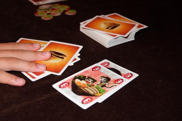 Dans ce jeu qui fait irrémédiablement penser au Uno, on dispose, à son tour de quatre possibilités : jouer une carte de sa main identique à celle posée sur la table, piocher autant de cartes que la somme des cartes au centre et les mettre dans sa main (ici Tristan en pioche 6), jouer une carte action ou jouer deux cartes de plats identiques pour changer le plat en cours (on en laisse une des deux et on défausse l'autre). A quoi servent les jetons en arrière-plan ? On y revient...
