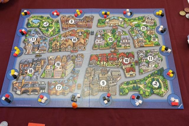 Au début de la partie, les cubes des joueurs sont répartis aléatoirement tout autour de la ville, à raison de 4 sur chaque cercle (case) du parcours que va sillonner le pion orange. Ci-dessus, il vient de s'arrêter sur une case où se trouvent 3 cubes noirs et 1 blanc, on va donc procéder à une vente pour se les adjuger et les répartir à son gré dans les quartiers de la ville. A noter qu'Angélique joue les noirs, Tristan les blancs, Damien (Alendar) les jaunes et moi-même les rouges...