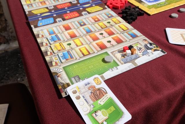 Chaque joueur dispose d'un plateau individuel, correspondant à son hôtel, sur lequel on a, en bas, la place pour placer jusqu'à trois clients à des tables de restaurant (ici j'en ai un de couleur verte, un touriste), avant que ceux-ci, une fois satisfaits (le lien souhaite deux cubes marron et deux blancs = deux strudel et deux gâteaux), aillent dans une chambre située plus haut (en associant la bonne couleur, le vert étant un joker, et à condition que la chambre soit prête, avec un serviteur près de la porte). Je ne parle pas encore de la piste de l'argent (en vert) ni des tableaux figurant sur le toit de l'hôtel...