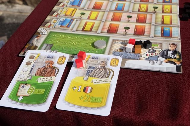 Petite vue de ma zone, maintenant que vous connaissez le jeu ! :-) Vous pouvez voir que je viens de satisfaire mon client jaune, un artiste, avec deux cubes rouges (=2 verres de vin). Du coup, je vais pouvoir profiter de son effet (gagner un cube de la couleur de mon choix et 2 couronnes), avant qu'il aille rejoindre une chambre jaune préparée pour lui dans mon hôtel...
