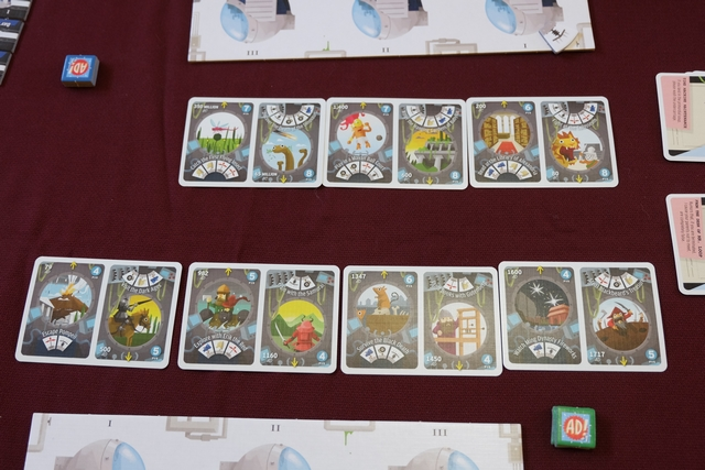 Au centre de la table sont étalées les cartes de voyages réalisables, classées chronologiquement (7 cartes de deux voyages chacune à 4 joueurs).