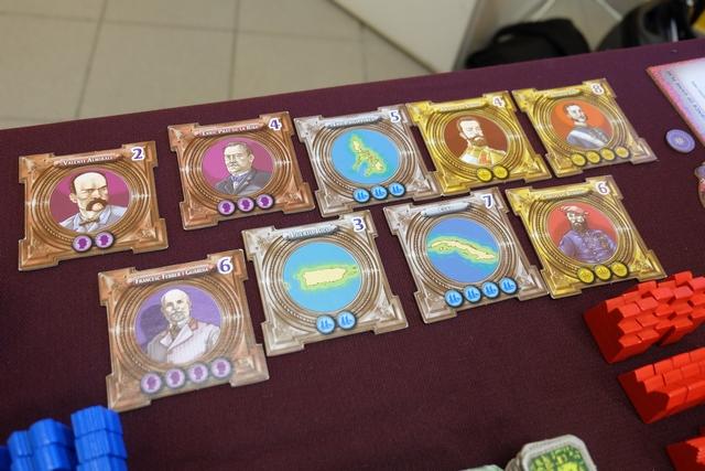 """Encore des composants de jeu ! Ci-dessus, voici les cartes d'influence que nous allons acquérir en payant les ressources indiquées. Une sorte de course à l'achat devrait se dérouler, sachant qu'on a intérêt à acheter les cartes correspondant à son """"alignement"""" familial (bonus de 2 PV à la fin). Par contre, en fonction de la progression de la bombe sur la piste en-dessous de """"Raval"""", les cartes pourraient disparaître avant d'avoir été vendues, voire, pire, être retirée du butin des joueurs si on en arrive à l'anarchie !"""