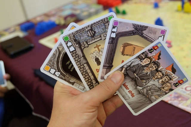 """Voici ma main de cartes, vue de face. Les cartes de popularité sont similaires aux cartes de cité (placement d'un bâtiment sur une tuile à la couleur indiquée), mais offre un avantage : soit un effet qui se cumule, soit un effet de type événement qui remplace la pose de bâtiment. Ça commence à devenir plus subtile cette affaire. ! A noter ma carte """"Labor Strike"""", laquelle va me faire sauter un tour lors de cette phase..."""