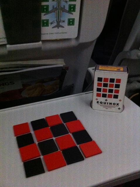 Preuve qu'on est dans un avion, la tablette sur laquelle on joue et la fiche de sécurité en arrière-plan... Donc, nous jouons à Equinox, un tout-petit jeu de Jean-Jacques Derghazarian , sorti voici déjà 8 ans... L'idée est de faire se connecter 7 de nos carrés, sans que l'ensemble du pavage n'excède un carré de 6 par 6. A son tour, basique, on déplace tout ou partie d'une ligne ou d'une colonne. Et puis c'est tout !