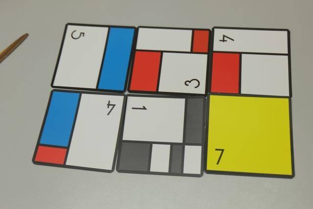 Étant le joueur avec le moins de cartes, 7 en l'occurrence, je contrains les autres joueurs à restreindre leur total au nombre de cartes maximal pour faire un rectangle, donc 2 par 3 = 6 cartes. Ci-dessus, voici l'œuvre magistrale de Romain...