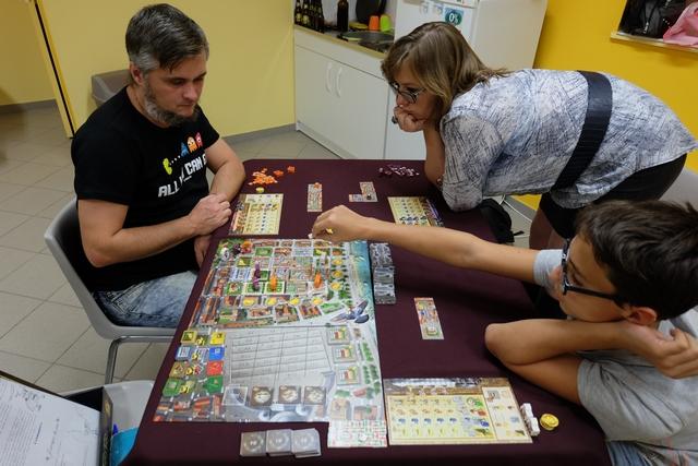 Nous découvrons ce jeu à 3 joueurs : Angélique avec les éléments violets, Tristan avec les blancs et moi-même avec les orange. Le jeu sent très bon ! Et c'est pas seulement parce qu'il y a des pizzas partout... ;-)