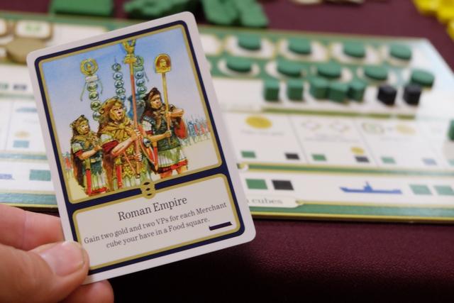 Une autre carte que j'ai prise : avec l'empire romain, je gagne 2 pièces et 2 PV pour chaque marchand de ma couleur (cubes verts) présents sur des ports donnant de la nourriture. Je prends donc 4 pièces et score 4 PV...