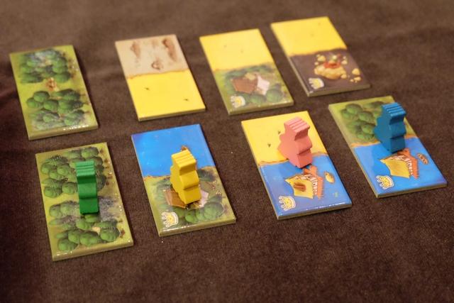 Lorsque les quatre pions sont sortis et placés sur les quatre tuiles initiales, la vraie partie débute avec l'ajout de quatre nouvelles tuiles juste à côté. Attention : les tuiles sont classées par ordre croissant en fonction de la valeur inscrite au dos, à partir de la boîte : de plus en plus intéressantes avec l'accroissement des valeurs. Le truc génial (Bravo Bruno !), c'est que le premier joueur à choisir sa tuile dans la deuxième ligne est celui qui était le plus près de la boîte (donc moi ci-dessus), et ainsi de suite ! Vraiment sympa ce mécanisme...