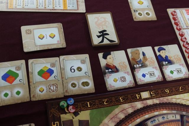 """L'étalage de cartes est constitué de deux séries : les cartes d'objectif, à gauche, avec les 3 que l'on peut prendre lorsque l'on aura notre marqueur de score qui franchira un symbole de parchemin (entre la case 4 et la case 5 ci-dessus), et, à droite, les cartes de personnages qu'on pourra recruter, lorsque l'un de nos chefs de famille s'arrêtera sur une action """"carte""""..."""