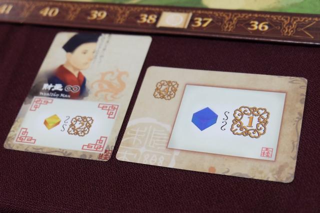 Je retourne donc ma carte d'objectif laquelle me permettra de gagner 1 PV à chaque tour où je prends au moins un cube bleu (et elle vaudra 4 PV à la fin). A côté d'elle, j'ai placé un personnage au pouvoir permanent : à chaque tour où je prends de l'or j'empoche 2 PV...