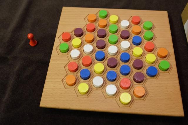Voici donc la configuration pour notre première partie, sachant qu'il y a un pion de positionnement à l'extérieur, lequel sera posé à l'endroit de son choix par le premier joueur. Juste une remarque sur la mise en place : les 7 pions d'une même couleur ne peuvent jamais être tous adjacents.