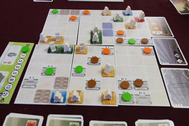 La mise en place du jeu, surtout pour une première partie, est vraiment longue et assez fastidieuse : on commence par étaler sur la table autant de plateaux que le double du nombre de joueurs (donc 6 pour nous aujourd'hui), puis nous positionnons les cartes par types de cartes : les bâtiments (en-dessous de la photo, à raison de 2 de chaque type à 3 joueurs), les cartes d'enchères (à droite, avec un étalage de 3 cartes et un réserve de 12), les cartes de développement (non visibles ci-dessus, avec 3 lots de 4 cartes) et les cartes de départ (lot remis à chaque joueur avec des cartes de parcelles notamment, correspondant aux cases pointées par un jeton à la couleur des joueurs, comme une sorte de pré-réservation). Quand je dis que nous avons trouvé ça fastidieux, c'est parce que ce n'était pas très naturel, avec un vocabulaire bien spécifique au jeu, et indiqué dans une règle que nous avons trouvée très austère...