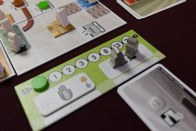 Le tour de jeu est assez simple finalement, même si on s'est posé de sacrées questions sur ce qu'on avait le droit de faire à son tour ! En premier, on réalise une enchère pour l'ordre du tour et l'acquisition d'une des trois cartes de l'étalage. En deuxième, chaque joueur joue une action du premier type ou prend 2 $. En troisième, chaque joueur réalise deux actions du premier type, ou une action et prend 2$, ou prend 2 $. Enfin, on peut jouer d'autres actions, du deuxième type, avant de clôturer le tour en refaisant sa main. Ci-dessus, lors de mon premier tour d'action, j'ai décidé de construire un bâtiment d'Industrie (jaune) sur une parcelle qui m'appartenait (A2). Savoir si c'est utile ou pas ? Pfff... dur à dire pour le moment ! En tout cas, j'ai empoché une nouvelle carte et étendu ma main à une capacité de 8 (mais il n'y a que deux joueurs qui pourront le faire).