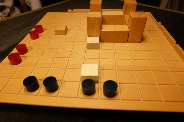 """A son tour, le joueur actif dispose de 3 points d'action, chacun d'entre eux permettant soit de déplacer un pion coloré (de deux cases en ligne droite à condition de monter ou descendre d'un niveau ou d'une seule case si on monte ou descend de deux niveaux), soit de placer un """"cheval"""" (carreau) sur une case d'intersection des baguettes extérieures au plateau (en face des fentes), soit de déplacer une baguette d'un cran. Il y a pas mal de solutions mais le plus difficile est quand même de visualiser comment avancer ses pions sans se faire avoir par le positionnement des chevaux..."""