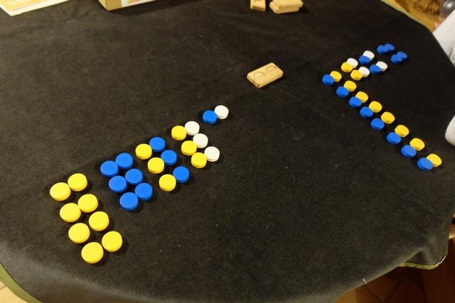 Au départ, chaque joueur prend 14 paires de jetons, lesquelles seront par la suite jouées dans les dominos. Le but du jeu ? Aligner 5 jetons à sa couleur, sachant que le blanc est neutre et comptabilisable, donc, par les deux joueurs. Ce soir, Tristan joue les jaunes et moi les bleus... A noter, quand même, que nos tirages de paires ne sont pas, mais alors pas du tout, équivalents ! Y a-t-il, pour autant, l'un de nous deux d'avantagé ?
