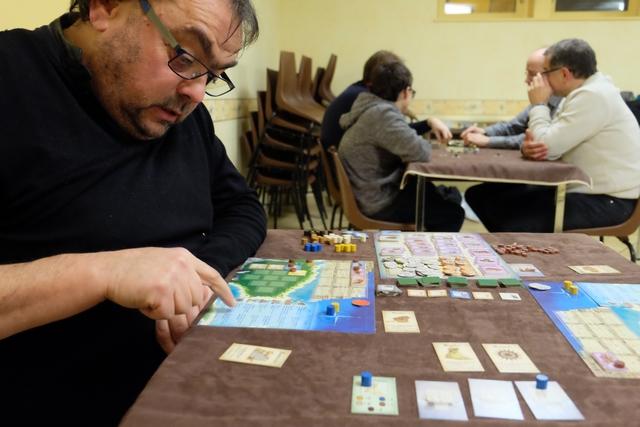 Jean-Luc s'évertue à lire l'aide de jeu en français positionnée sur son plateau allemand. Mais, en fait, la logique du jeu fait que ça va quand même assez vite...