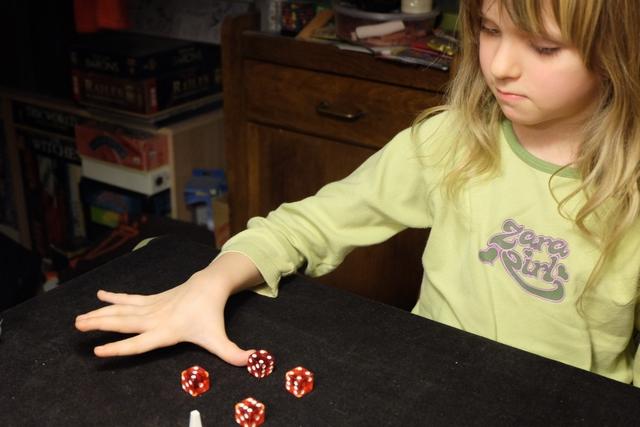 Ca y est !!! Leila découvre vraiment le jeu en procédant à son premier lancer de dés. Pour s'y retrouver et essayer des combinaisons, elle place les 4 dés en carré et les ajoute de proche en proche.