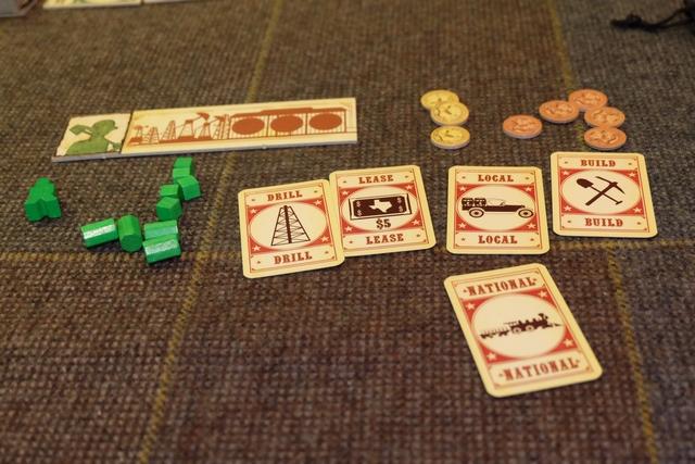 """Chaque joueur reçoit en début de partie une tuile avec trois emplacements de stockage pour ses cubes extraits, ainsi qu'un set de pions, 20 dollars en pièces et une main de 5 cartes d'action. La mécanique est basée sur des actions limitées sur le plateau (une ou deux places en général) sur lesquelles on se place à tour de rôle (une par joueur et par tour), suivie d'une de ces cartes jouées face cachée, apportant ainsi une deuxième action pour le tour. Le tout est d'éviter de jouer la carte """"National"""" en même temps que les autres, puisque celle-ci permet de vendre plus cher ses cubes à condition de ne pas être beaucoup à l'avoir choisie au même moment. Du guessing, donc, et du rythme à trouver en décalage des autres joueurs..."""