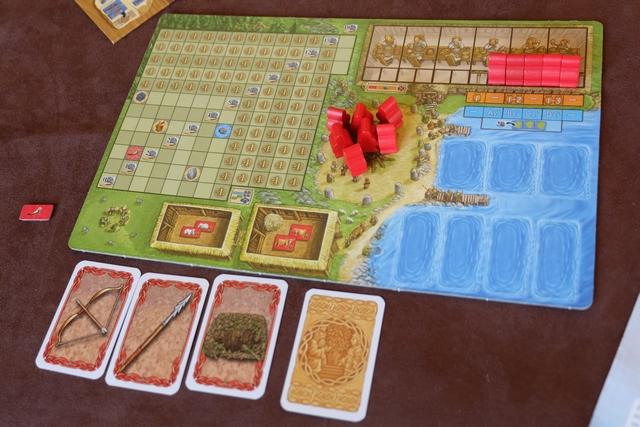 Chaque joueur reçoit un plateau individuel en début de partie, sur lequel il va tenter de développer sa tribu (les chefs vikings rouges pour moi). A gauche se trouve la grande zone sur laquelle je vais essayer de placer des butins collectés (verts ou bleus), tout en laissant visibles des revenus et des bonus, et en couvrant les fatidiques -1 PV ! En-dessous, je vais pouvoir placer des bêtes d'élevage (moutons et/ ou vaches). A droite, dans mon port, je pourrai amarrer 3 baleiniers maximum et un total de 4 autres bateaux (knarr ou drakkars). Au-dessus se situe la table du banquet, avec également les vikings dont j'en récupérerai un en début de chaque tour (total de 6 pour la partie courte du jour). Enfin, au centre, il y a le centre des affaires où sont stockés mes vikings utilisables pour le choix des actions du tour...