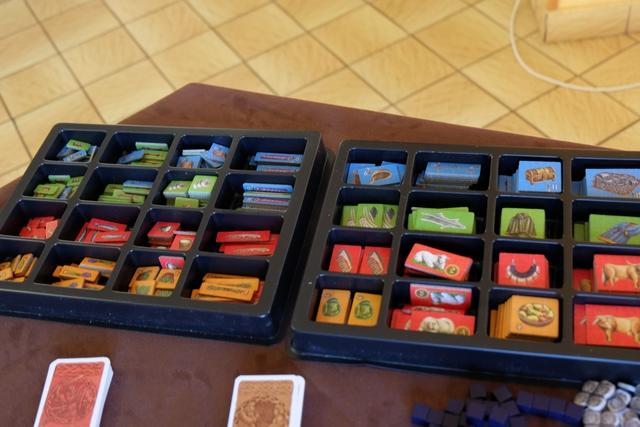 Bravo à l'éditeur qui propose directement dans la boîte ces deux casiers pour stocker les différentes ressources ! En bas, on a les ressources les plus faibles (orange) et une partie des animaux), au-dessus les rouges un peu plus intéressantes, au-dessus les vertes et enfin les bleues, ces deux dernières étant requises pour remplir sa grande zone sur son plateau individuel, en respectant deux règles : deux tuiles vertes ne peuvent se toucher que par les angles, les bleues pouvant se placer n'importe comment. Simple...