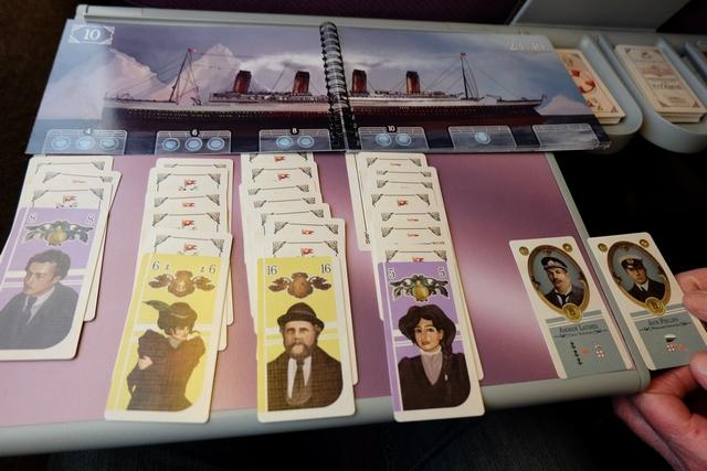 """Au début, il est 23h40, et les premières avaries ne vont pas tarder à survenir suite au choc entre le paquebot et un iceberg. Le Titanic est divisé en 6 ponts, le premier composé de 3 cabines, le second de 3 cabines, le troisième de 2 cabines, le quatrième de 2 cabines, le cinquième d'une seule cabine et le sixième d'aucune cabine ! En-dessous du premier pont on a étalé face cachée 4 cartes puis retourné celle du bas, pour le deuxième pont on en a mis 6, pour le troisième 8 et pour le quatrième 10. Les cartes étalées correspondent aux passagers que l'on essaie de sauver, ceux-ci étant divisés en deux couleurs (violet et jaune) correspondant aux deux """"classes"""" de passagers (la première avec des valeurs de 1 à 13, la seconde avec des valeurs de 1 à 17). Comme dans une réussite, il faut petit à petit extraire les cartes en ordre croissant et / ou décroissant (on y reviendra). Sur la droite, vous pouvez voir le personnage que nous incarnons, chacun, à savoir Andrew Latimer pour moi et Jack Phillips pour Gérard. Chacune a un petit pouvoir spécial."""
