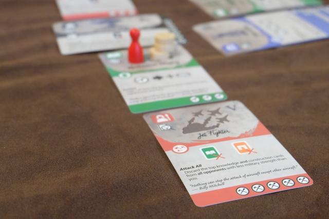 Les cartes montent en puissance comme en atteste celle du bas, les avions de chasse, puisqu'elle fait défausser une carte verte et une carte orange à TOUS les joueurs moins fort militairement que celui qui terminera cette carte. Ca fait peur...