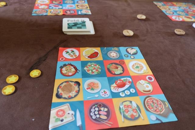 Voici donc les composants du jeu, magnifiques soulignons-le : une serviette imprimée des deux côtés (les mêmes plats aux mêmes endroits), trois jetons d'étoiles à conserver le plus longtemps possible (on en perd un à chaque fois qu'on est le dernier à réussir), des cartes au centre (les bleues dites faciles, les rouges dites difficiles) et, enfin, de jolis jetons en bois à prendre quand on a fini sa commande (un de moins que de joueurs).