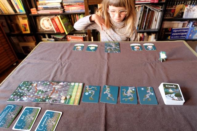 Nous jouons à deux joueurs, Leila à lunettes rose clair et son papa... Ca va être un peu dur pour elle, les cartes d'objectifs étant à bien lire et à bien comprendre, mais on décide de lui faciliter la tâche en étalant devant elle les quatre qu'elle a reçues après les avoir explicitées. Chacun va développer son propre arbre, branche après branche, alors qu'un étalage de quatre cartes est exposé au centre, qu'une carte de saison affecte la manche en cours et qu'une grande piste de scores est disposée à gauche.