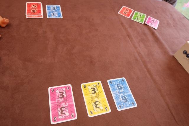La règle est limpide et subtile, tout en étant particulièrement déconcertante : c'est un jeu de plis dans lequel on n'est tenu à aucune règle (couleur, valeur, on fait ce qu'on veut), la plus forte carte (valeur) empochant le pli. Ce qui est nouveau c'est que les cartes prises sont empilées couleur par couleur dans l'ordre de la récolte. En fin de manche, c'est-à-dire quand les joueurs auront joué toutes leurs cartes, seule la carte placée au-dessus de chaque pile comptera pour le score ! Titillant non ? Ci-dessus, vous pouvez voir les trois cartes initialement choisies par chacun de nous pour amorcer les piles (on aura 10 cartes à jouer ensuite pour la manche).