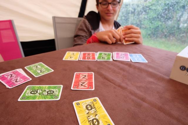En cas d'égalité dans la valeur de la carte jouée (ci-dessus le 0 jaune et le 0 vert), le premier joué vaut plus que l'autre. Ci-dessus, Tristan couine car avec son 2 rouge il va recouvrir son 8 rouge, avec mon 0 jaune il va recouvrir son 4 jaune et avec le 0 vert joué par Leila c'est son 9 vert qui saute. Ah la la, pas facile, hein ! ;-)