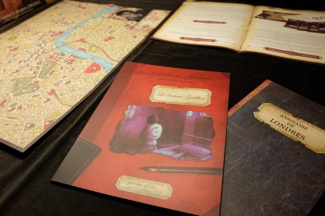 Afin de mener à bien notre enquête, nous disposons des divers outils suivants : le scénario à couverture rouge, le plan de Londres, l'annuaire de Londres, le livret de règles avec les informateurs au dos, et, non visible ci-dessus, le journal du jour (13 septembre 1898).