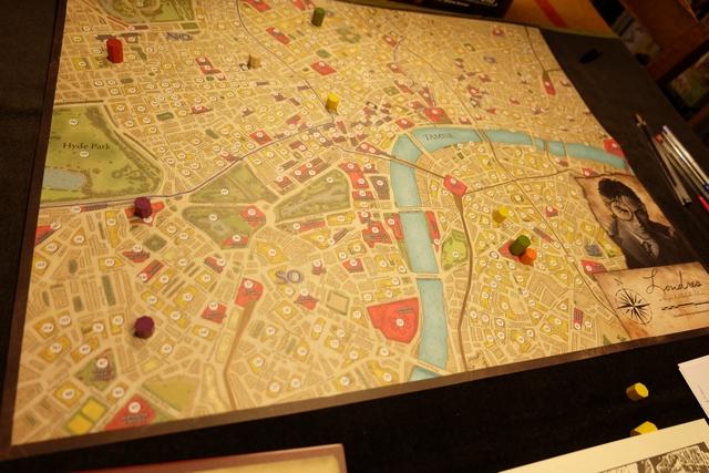 Une fois lue l'introduction du scénario du jour, chez Holmes, on prend l'idée de noter sur le plan de Londres tous les lieux indiqués d'une manière ou d'une autre par des cylindres colorés (même couleur = deux lieux pour le même indice). Cela nous donne une vue spatiale de la situation et, sans avoir jamais joué au jeu, on se dit que ce peut être une furieusement bonne idée en cas de lien géographique entre les indices. Un peu comme dans les séries policières quand les enquêteurs placent de petits drapeaux sur des lieux identifiés...