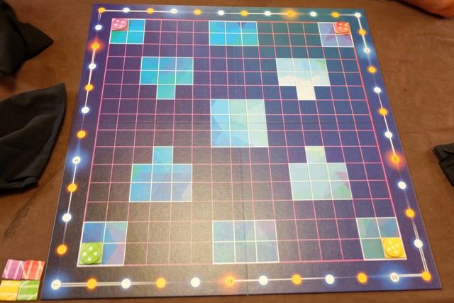 Le plateau de ce jeu abstrait est vraiment très dépouillé : un quadrillage de 15 cases par 15 cases avec soit des couloirs (cases bleu foncé) soit des salles (cases bleu clair). Chaque joueur démarre d'un coin du plateau avec une tuile de départ carrée à sa couleur et un premier jeton de lumière posé dessus. Chacun dispose d'un sac de pioche dans lequel il a glissé tous ses jetons de lumière, ces derniers étant bifaces, avec 1 et 6, 2 et 5 ou encore 3 et 4. Je reviendrai sur leur utilisation sous peu...