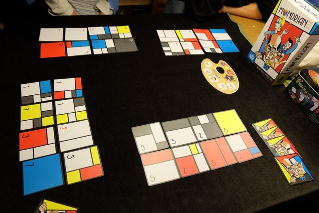 Chacun construit devant lui un tableau estampillé Mondrian de 2 cartes par 4 cartes, les joueuses en possédant le moins en ayant précisément 8. Leila et moi défaussons, respectivement, 2 et 4 cartes... Bien entendu, chacun construit sa défausse et son tableau sans observer ce que font les autres (important pour les majorités)... Puis nous comptons les points : valeurs des cartes + points liés aux majorités du nombre de cases par couleur).