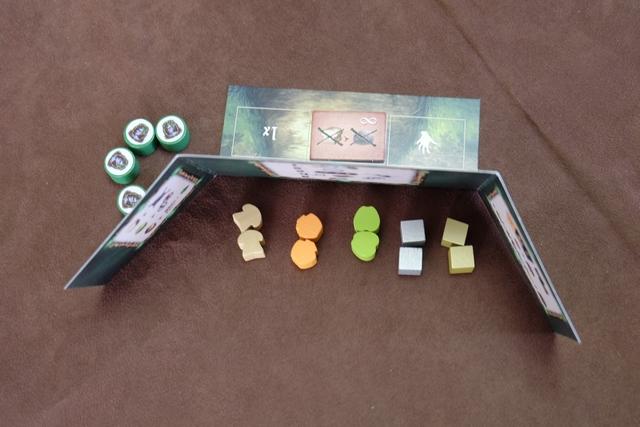 Chaque joueur dispose d'un paravent derrière lequel il stocke ses ressources collectées et ses tuiles de récompense acquises. Ci-dessus, en début de partie, comme je ne suis pas le chouchou de la reine (premier joueur), j'ai 2 pains, 2 miels, 2 pommes, 2 lingots d'argent et 2 lingots d'or. Sur le devant du paravent, une zone divisée en trois cases, va permettre à chaque joueur d'avoir des pouvoirs particuliers : un one-shot, un lié au vol dans les villages et un permanent qu'on choisit au départ (et qui pourra être échangé par la suite). En ce qui me concerne, j'ai choisi celui qui me permet d'enlever gratuitement les pierres qui seront attachés aux pieds de mes pixies dans ma mine, au lieu de dépenser du pain pour cela. Enfin, à gauche, vous voyez mes 4 pions d'action qui me permettront de faire des actions sur le plateau.