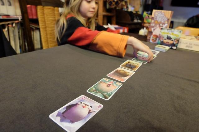 Elle sait s'arrêter à temps la bougresse ! Elle empoche donc les 5 cartes ci-dessus et a donc le droit d'en poser 3 sur la table (total - 2), les autres rejoignant sa main. Les joueurs chez qui elle a pioché complètent leur main à 7. Le but du jeu est de constituer 3 séries de 3 cartes identiques sur la table à 4 joueurs...