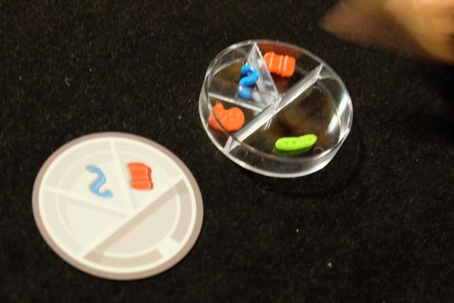 """Petit exemple avec mon pétri complété : j'ai placé la """"valise"""" rouge, le """"serpent"""" bleu, puis un """"steak"""" rouge, dans les trois secteurs les plus petits (zone des microbes). Dans le grand secteur, en revanche, il faut placer l'antidote, à savoir un microbe qui ne soit ni de la même couleur, ni de la même forme que ceux présents dans les petits secteurs. Du coup, j'ai mis le """"cornichon"""" vert. Compris ?"""
