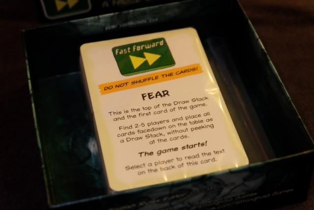 Une fois la boîte ouverte, au cas où on n'aurait pas compris, il est indiqué de ne pas mélanger les cartes ! Et, histoire de bien valider le truc, on nous précise que voici la première carte de la pioche et que le jeu va démarrer tout de suite après le choix d'un premier joueur qui lira le dos de cette carte...
