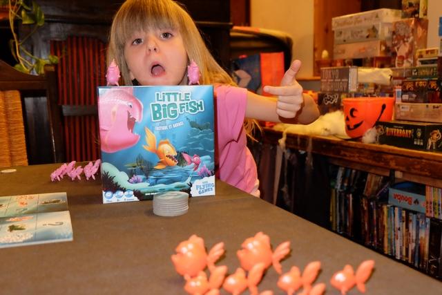 Leila imite les poissons de la boîte, non sans un certain talent, elle-même vêtue de rose comme sa série de poissons...