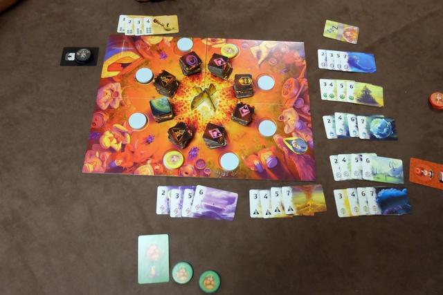 Dans ce jeu, où le thème malheureusement est absolument impossible à croire, on essaie de reconstituer des histoires qui se racontent autour du feu. En fait, basiquement, on essaie de collecter des tuiles colorées et de les assembler (les mêmes, des différentes) pour récupérer des cartes objectifs. Ce qui est très sympa, c'est la mécanique pour récupérer ces tuiles, mais j'y reviens...