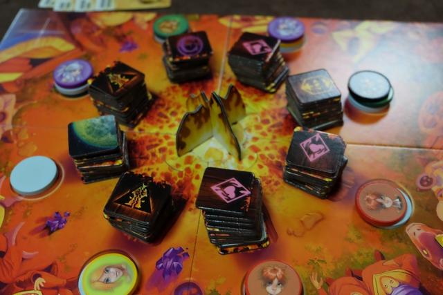 En début de partie, chacun choisit un personnage associé à un pouvoir particulier. Puis, chacun place ses deux disques autour du feu (trois pour moi, puisque c'est le pouvoir du joueur vert d'en avoir un troisième). A son tour, le joueur actif choisit une pile où il est présent et égrène, comme à l'awalé, les disques dans le sens des aiguilles d'une montre. Enfin, tous les pions au sommet des piles permettent aux joueurs de récupérer la tuile du dessus. Au lieu de faire ça, le joueur actif peut opter pour la réalisation d'une carte objectif avec certaines de ses tuiles déjà collectées.