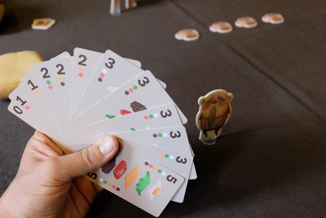 Chaque joueur reçoit une main de cartes, douze à 3 joueurs, dont une carte 0 et une carte 5. Sur chaque carte figure un numéro, la quantité d'ingrédients dans le hamburger, et des pastilles colorées, les ingrédients en question (viande, tomate, fromage, salade et œuf). On a aussi une figurine représentant son personnage lorsque celui-ci ira faire la queue devant le restaurant.