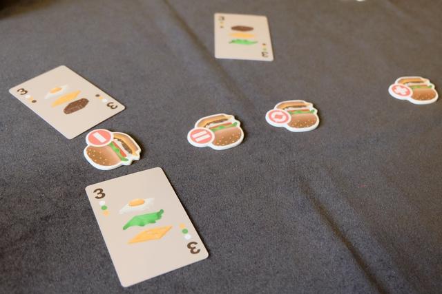 Chacun a sélectionné une carte de sa main, face cachée, au plus près du hamburger prévu par le cuisinier, sachant que sont tolérés les écarts suivants : un ingrédient de plus ou de moins, ou la bonne quantité d'ingrédients mais avec une seule inversion. Bien sûr, on peut très bien jouer la carte parfaite, si on l'a. Ci-dessus, Leila s'est trompée car elle a joué trois ingrédients, mais en plus, il y a une inversion, donc sa carte va être placée face cachée à sa gauche. Tristan, grand comique, ne joue pas la bonne carte, qu'on attendait, mais une carte avec un ingrédient en trop, tout comme moi ! Du coup, on fait la queue devant le restau, mais il sera servi avant moi (ordre du tour)...