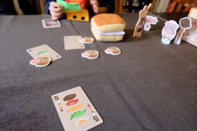 Je m'en sors miraculeusement, mais je subis un autre effet que je n'avais pas anticipé : Leila fait un hamburger avec les 5 ingrédients, il ne me restait que le 5, Leila joue son 5 aussi et on va faire la queue au restaurant (alors que c'était ma dernière carte) ! De fil en aiguille, je ne m'en sors pas et c'est Tristan qui s'en tire... Blasé.