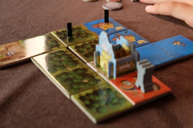 Tristan réalise une magnifique double levée d'impôt en plaçant ses deux chevaliers sur les deux cases de sa dernière tuile posée : 6+4 = 10 sous d'un coup ! A noter la présence d'une tour sur une de ses cases rouges, celles-ci constituant une autre nouveauté du jeu, à savoir qu'elles sont indiquées sur les tuiles de bâtiments et qu'elles peuvent permettre d'avoir la Reine dans son domaine (le joueur majoritaire en nombre de tours), abaissant les coûts d'achat de 1 et, surtout, de compter pour une couronne supplémentaire si on l'a toujours en fin de partie !