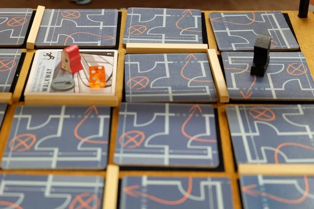 Sur chaque étage de la banque se trouve un garde qui fait sa ronde entre sa case de départ (tirée au hasard au départ) et sa case d'arrivée (tirée au hasard aussi et symbolisée ci-dessus par le dé orange affichant 2, la capacité de déplacement du garde par tour). Les tuiles sont face cachée car on ne sait quelles pièces s'y trouvent. Les bâtonnets représentent les murs et créent des couloirs (fixés par la règle de mise en place). Enfin, les joueurs entrent par l'escalier venant du sous-sol (jeton gris) et tentent de se dissimuler au maximum. Pour le moment, seul Pierre, notre acrobate rouge, est entré en jeu...