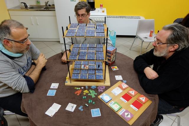 Oui, ça a de la gueule cet immeuble de trois étages, je sais et en suis bien content ;-) En même temps, je ne vois pas bien comment jouer à ce jeu sans cet édifice offrant une bonne vision 3D : à plat sur la table, je n'y crois guère... Comme vous le voyez, nous découvrons ce jeu à 4 joueurs, Yohel avec The Juicer en violet, Romain avec The Rook en gris, Pierre avec The Acrobat en rouge, et moi-même en vert avec The Hacker.
